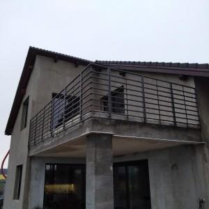 Vysoké robustní kovové zábradlí na terase nového rodinného domu
