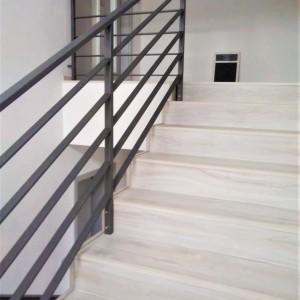 Černé kovové zábradlí u schodiště v domě