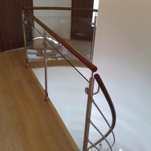 Moderní kovové zábradlí u obloukového schodiště v domě