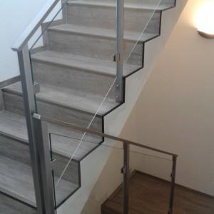 Moderní kovové zábradlí u schodiště domu se skleněnou výplní
