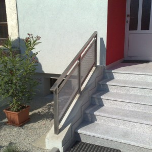 Malé ale účelné kovové zábradlí u vchodových schodů do budovy