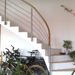 Kovové zábradlí u obloukového schodiště v rodinném domě