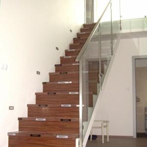 Moderní kovové zábradlí u vysokého schodiště v budově