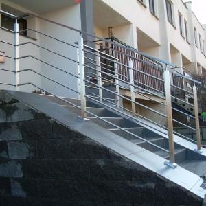 Mohutné kovové zábradlí u schodiště před domem
