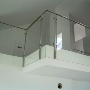 Kovové zábradlí v kombinaci se sklem uvnitř budovy