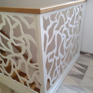 Bílé kovové zábradlí uvnitř domu v okolí schodiště