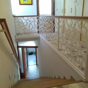 Bílé kovové zábradlí ve speciálním vzoru uvnitř domu