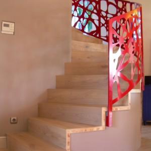 Kovové zábradlí červené barvy kolem schodiště v domě