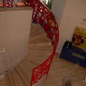 Umělecké červené zábradlí kolem schodiště v interiéru domu