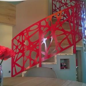 Kovové červené zábradlí kolem schodiště