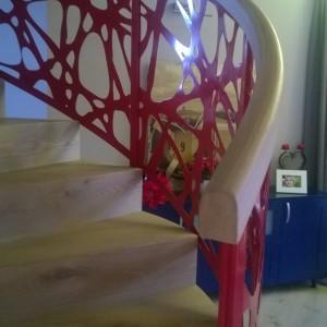 Červené kovové zábradlí u kruhového schodiště
