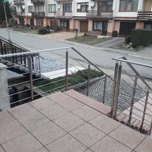 Kovové zábradlí u terasy a schodiště před rodinným domem