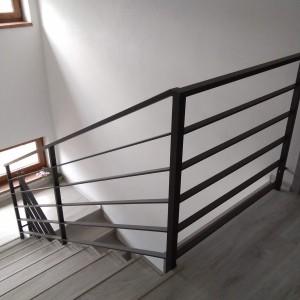 Pohled na tmavé kovové zábradlí u schodiště v domě