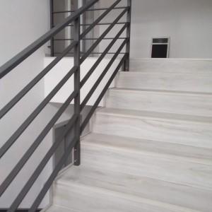 Tmavé kovové zábradlí u schodiště uvnitř budovy
