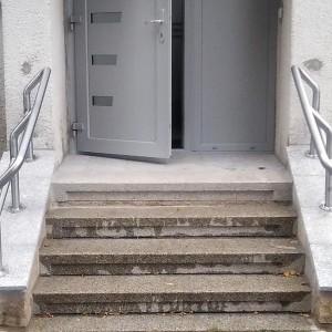 Dodatečně zbudované kovové zábradlí u malého schodiště