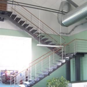 Systém zábradlí u vysokého schodiště uvnitř průmyslové budovy
