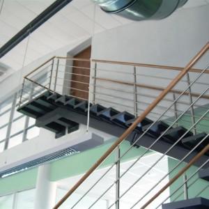 Systém kovového zábradlí u vysokého schodiště uvnitř průmyslové budovy