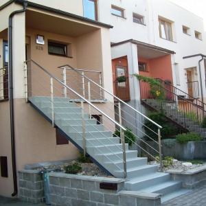 Pevné kovové zábradlí u vstupního schodiště do rodinného domu