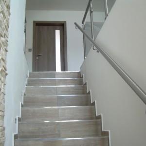 Jednoduché kovové zábradlí kotvené přímo do zdi podél schodiště v domě