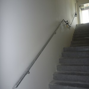 Jednoduché kovové zábradlí kotvené přímo do zdi u schodiště v budově