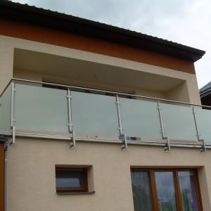 Kovové zábradlí na terase domu s neprůhlednou skleněnou výplní