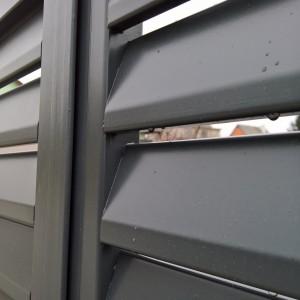 Detail kovové brány s mohutnou konstrukcí pomocí lamel