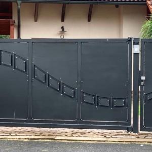 Detail tmavé vjezdové brány, na které je i designový prvek