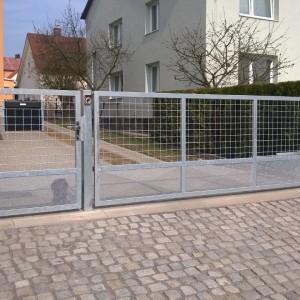 Elektricky ovládaná vjezdová brána a vstupní branka jednoduché kovové konstrukce u rodinného domu