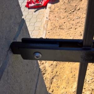 Detail kovové vjezdové brány, kotvení do pilíře