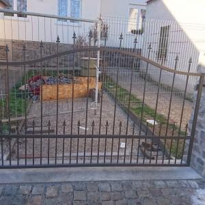 Železná brána s dekorativními prvky u rodinného domu
